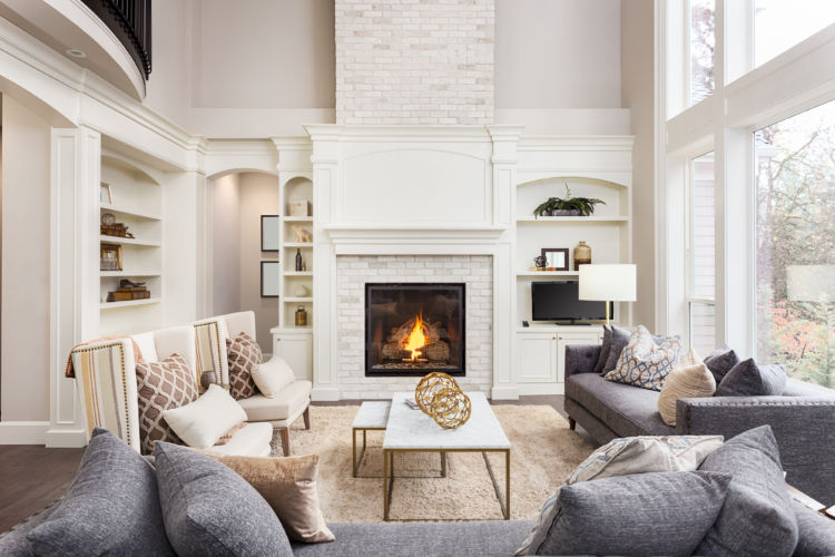 Beautiful living room interior with tall vaulted ceiling, loft area, hardwood floors and fireplace in new luxury home. Has large bank of windows, traditional style