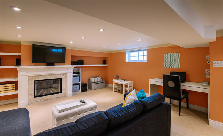 Living room make in basement, fireplace, tv, orange walls
