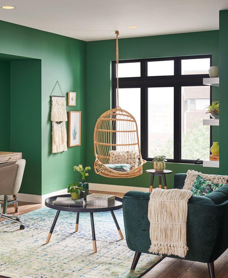 Living room, bold green walls, big window, hanging straw armchair
