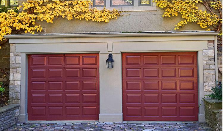 dark red double garage doors, part of grey walls, yellow leaves above garage doors