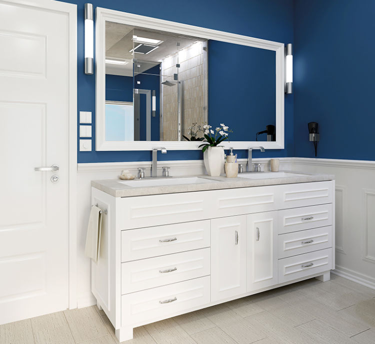 part of bathroom, blue walls, white cabinets and big mirror over it