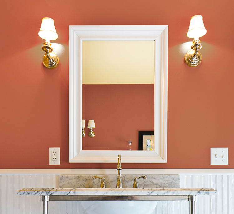 bathroom lavatory with marble top, clay color wall and mirror in the center