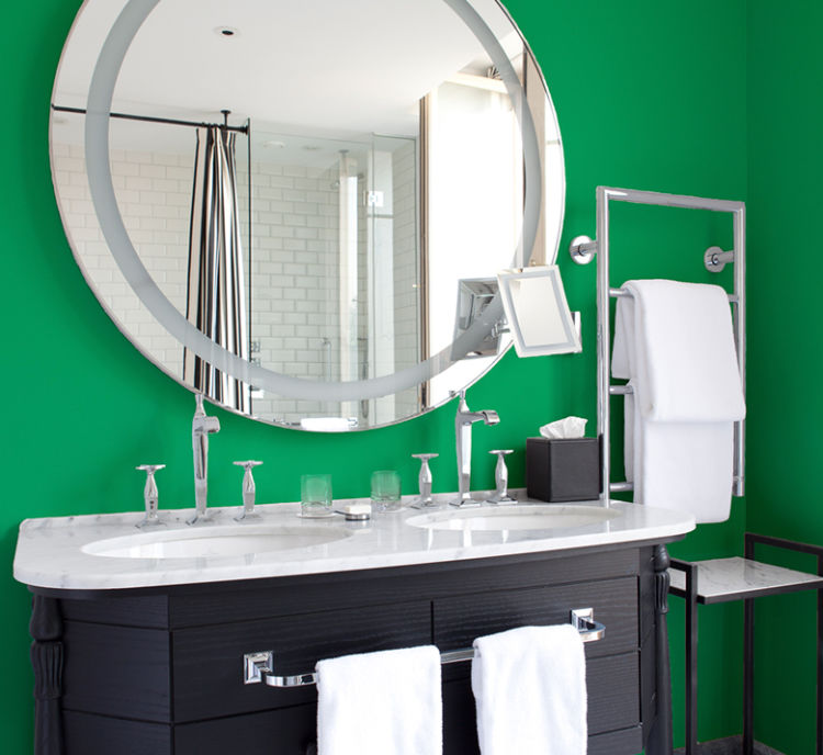 bathroom double lavatory with black wooden cabinets, sharp green walls, rounded mirror