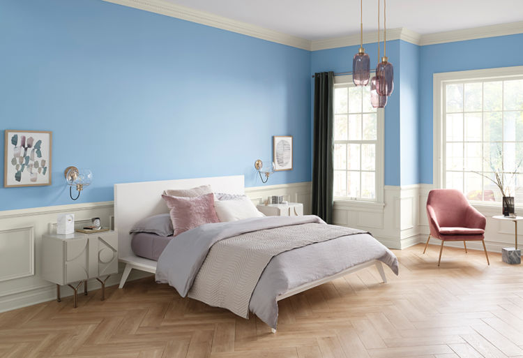 bedroom from angle, bed, blue walls and 2 widnows