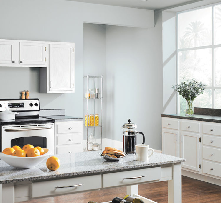 light kitchen with white cabinets, white table with granite top, light blueish gray walls