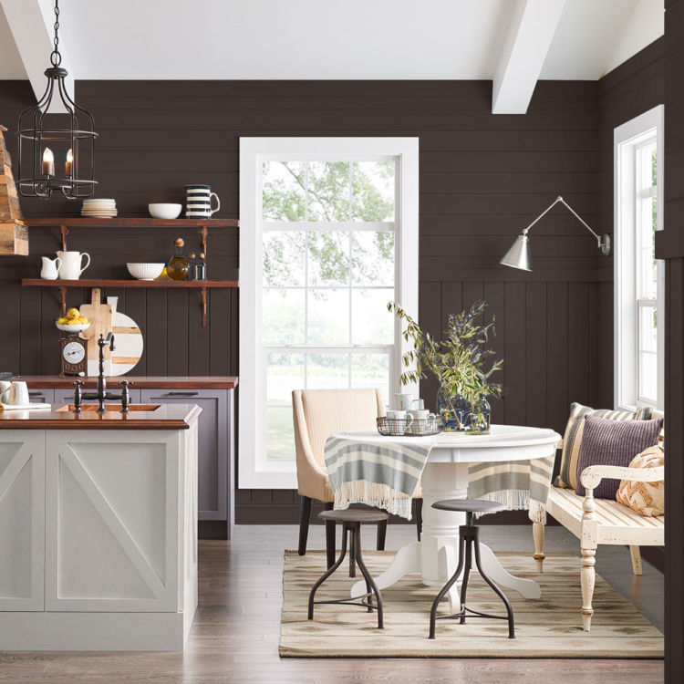 kitchen with dining table, white cabinets, dark brown wooden walls