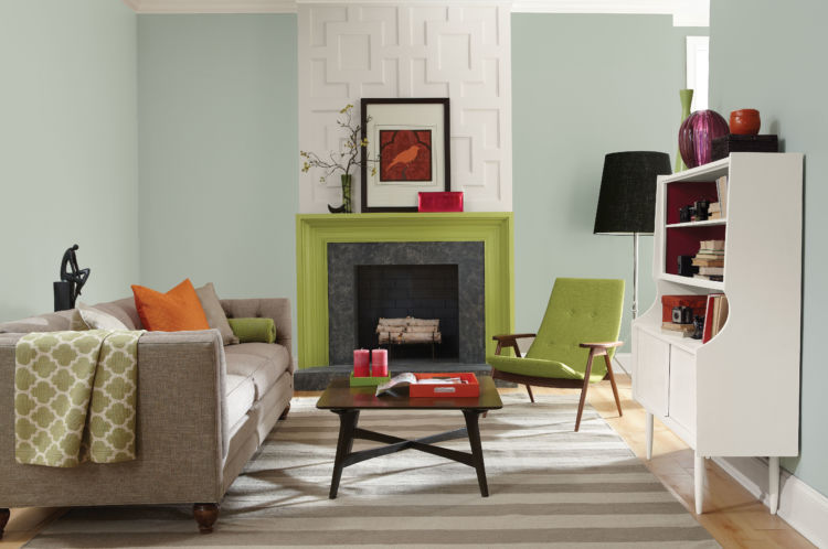 living room, fireplace with green moldings in the center, chair with same shade of green, table and couch