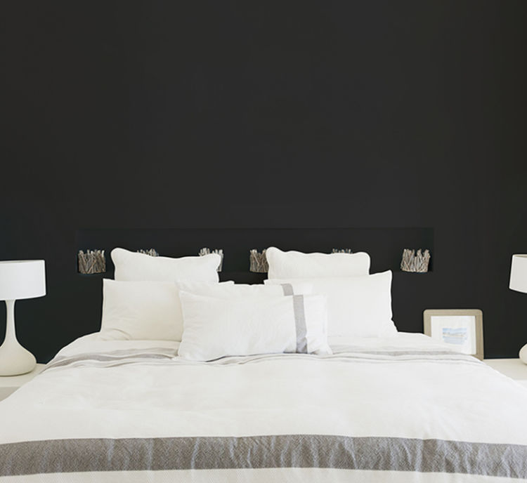 bedroom, bed with white bedding, tricorn black wall