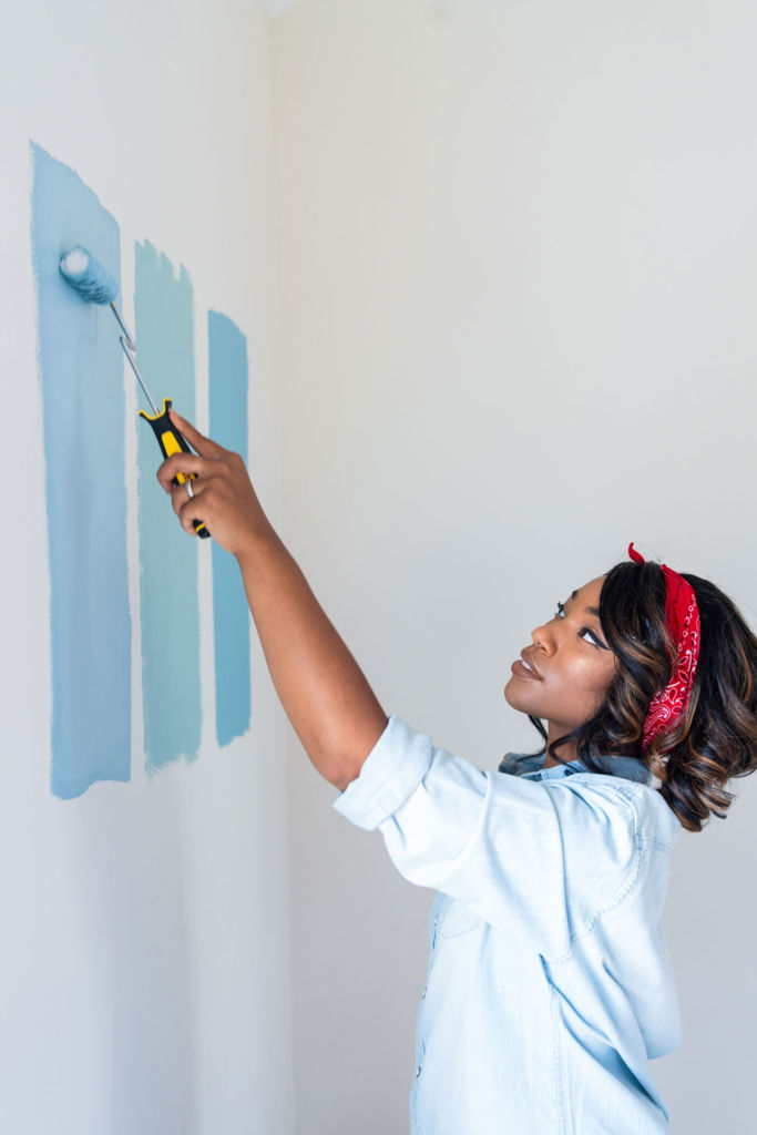Woman applying different shades of blue on white wall with paint roll