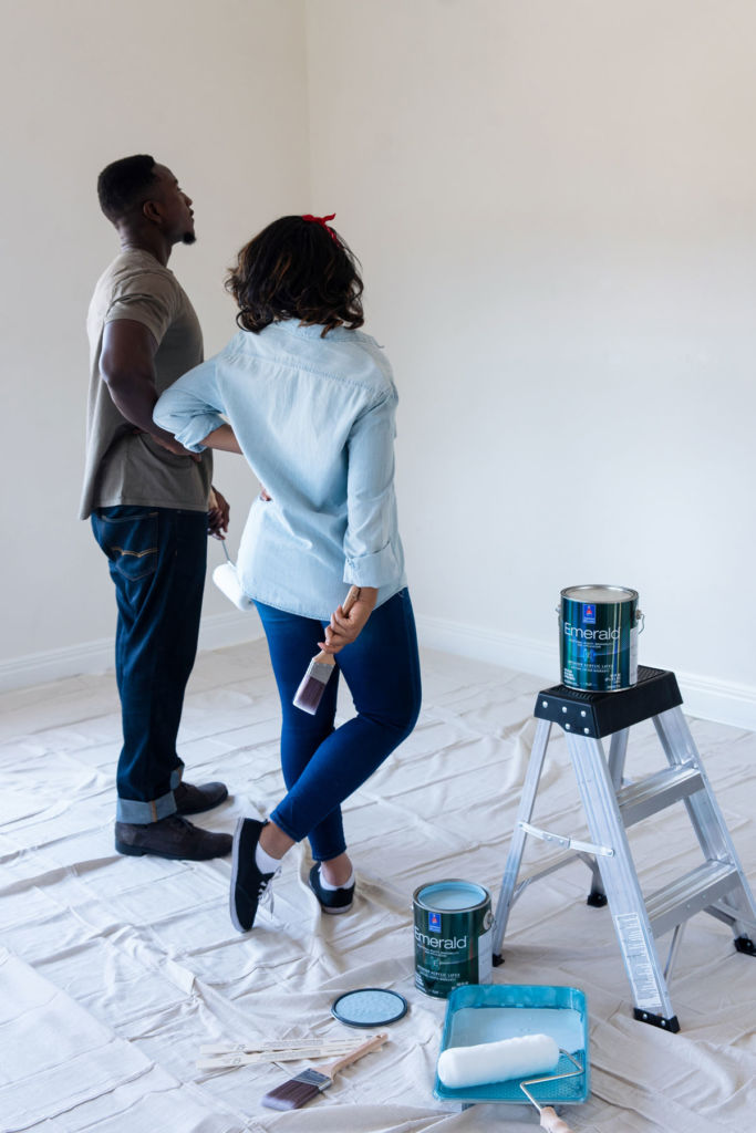 Man and woman looking at white wall with paint brush and paint roll