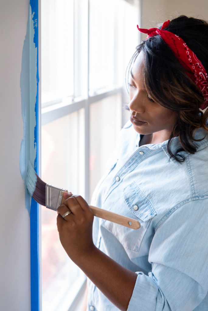 Woman painting wall next to window with brush