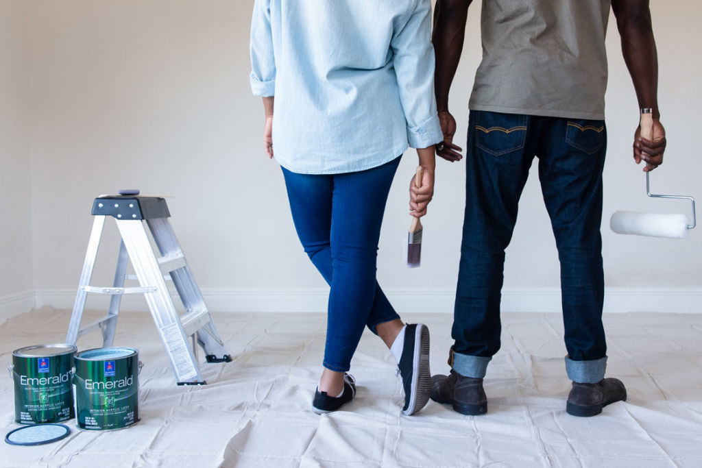 Man and woman standing against white wall with paint brush and paint roll in their hands, no heads visible - image cut on chest height