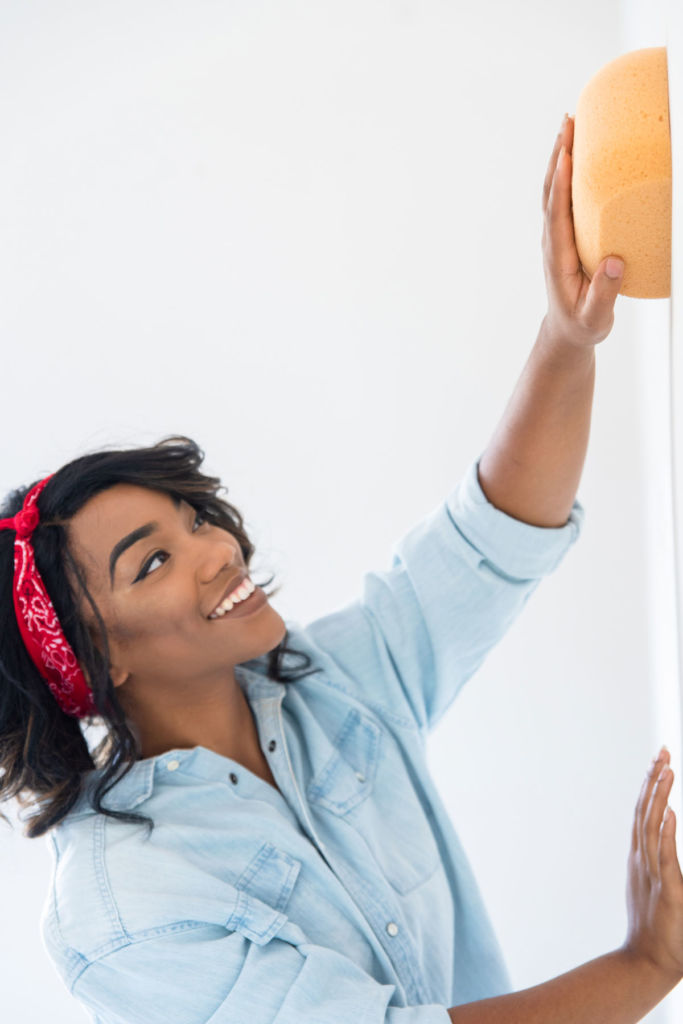 Woman preparing wall for painting with yellow sponge