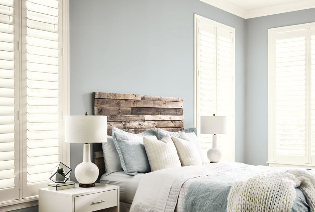 part of bedroom, light blue walls, bed with wooden board