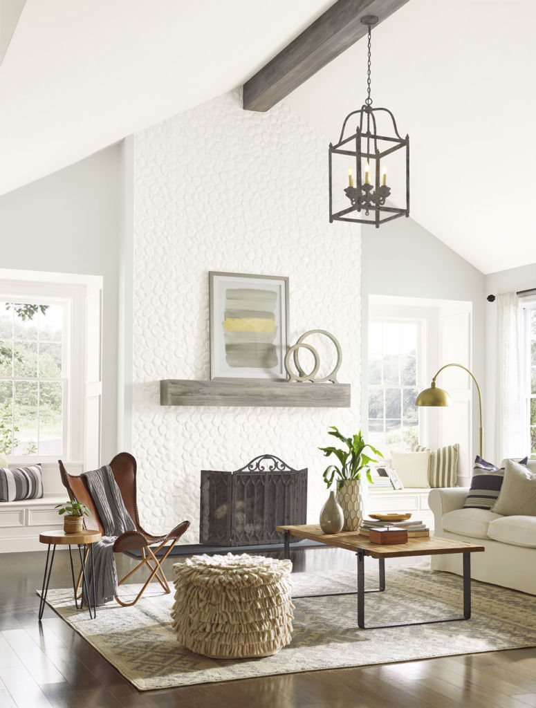 Living room with height diagonal ceiling, white walls, fireplace, some chair table and couch