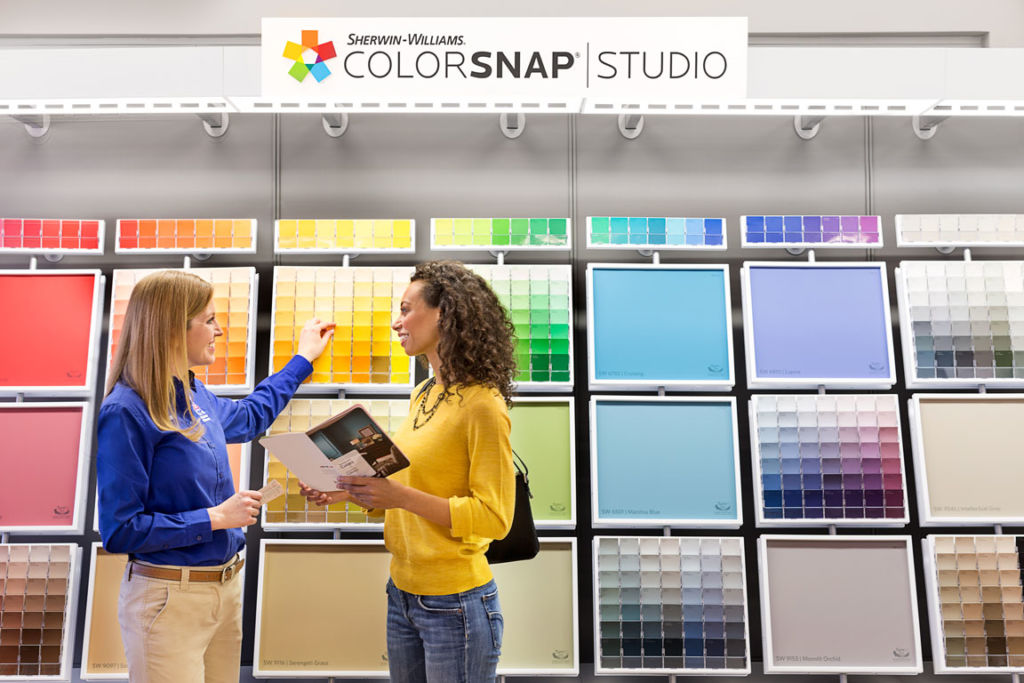 Two women by color swatch display in hardware store