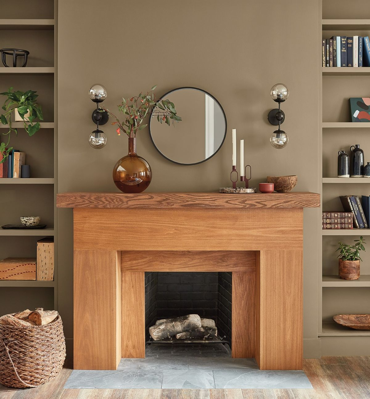 wooden fireplace, rounded mirror above