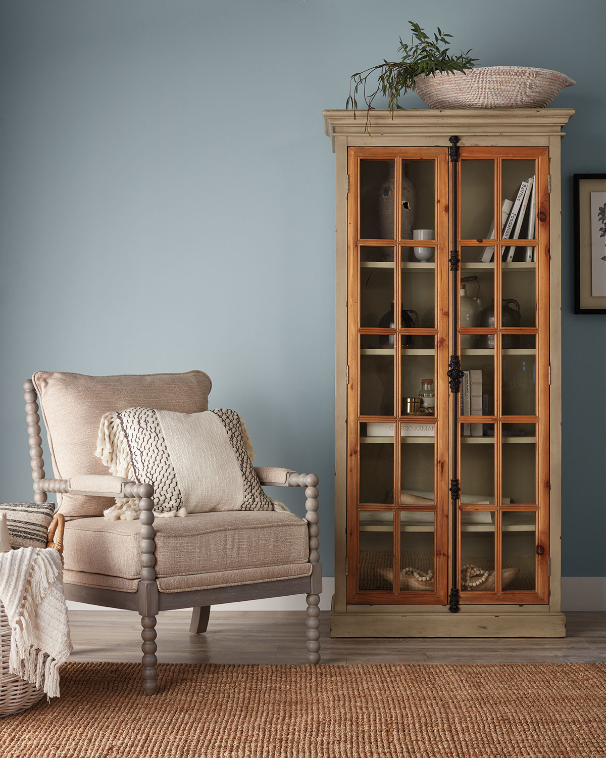 wooden cabinet with glass doors and books inside, armchair