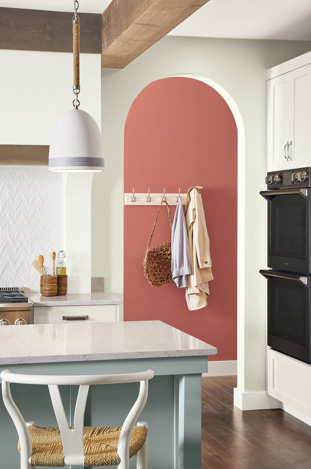 Part of the kitchen, part of countertop with white marble top, hallway with peach wall and wall hanger seen through arc opening