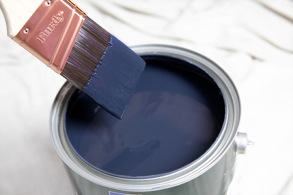 can of blue paint with paint brush