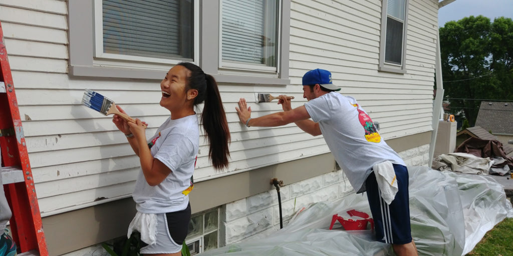 young people painting a house outside