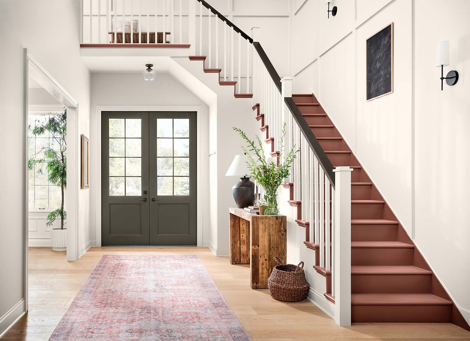 Entryway with stairs painted in Canyon Clay SW 6054.