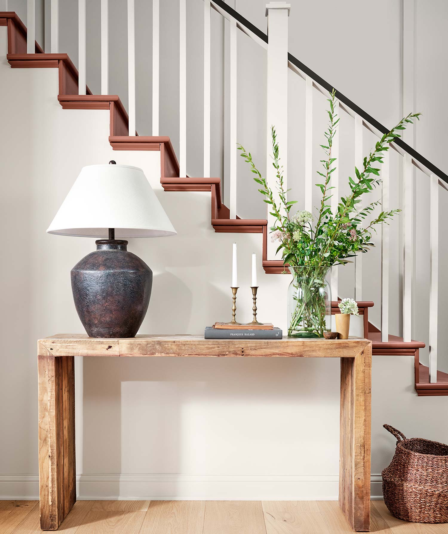 Wooden table with plant, lamp, and candle near stairs painted in Canyon Clay SW 6054.