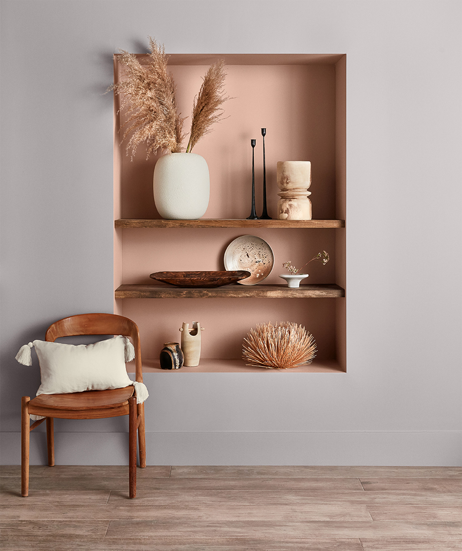 Shelf holding natural, earth-tone objects painted Hushed Auburn SW 9080 set in a wall painted Mystical Shade SW 6276.