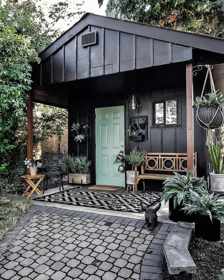 calming room makeovers: cottage exterior painted in Tricorn Black and nestled in trees