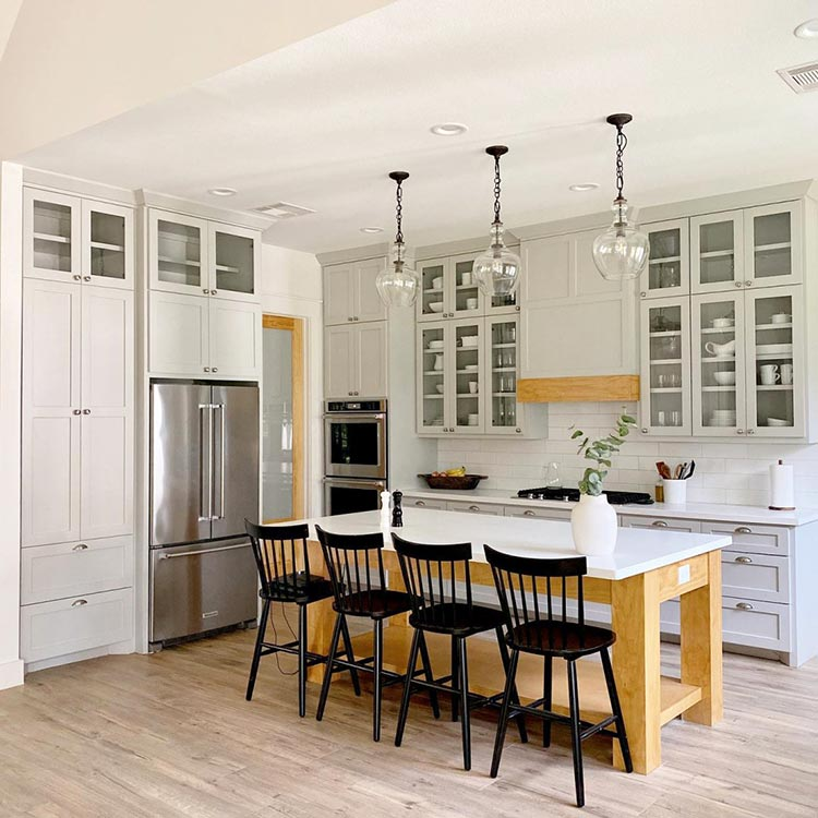 A calming farmhouse kitchen with lofty ceilings and floor-to-ceiling cabinets painted in Light French Gray