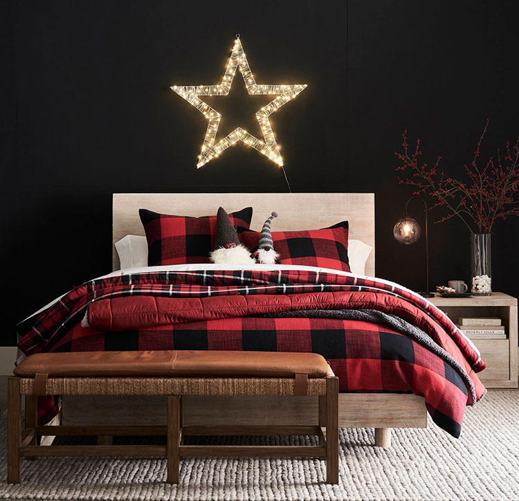 cozy bedroom with a dark accent wall light-up star and holiday throws