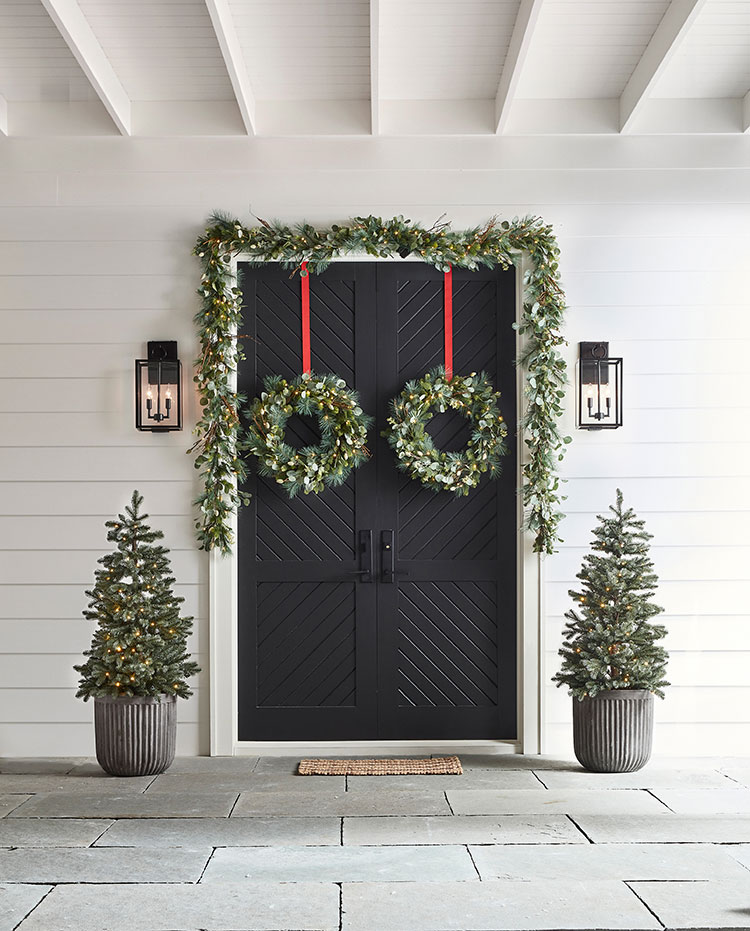 bright white entryway with dark doors and lit-up holiday greenery