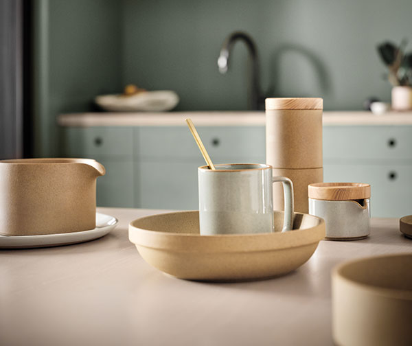 Earth-toned cups and mugs on a kitchen counter.