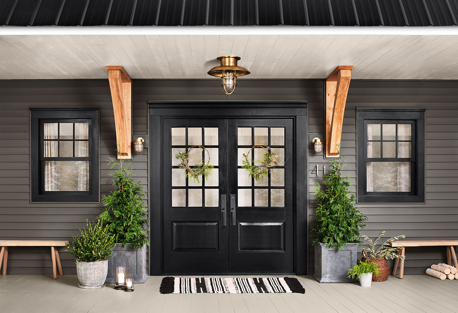 Home exterior with dark double doors and walls painted Urbane Bronze SW 7048.