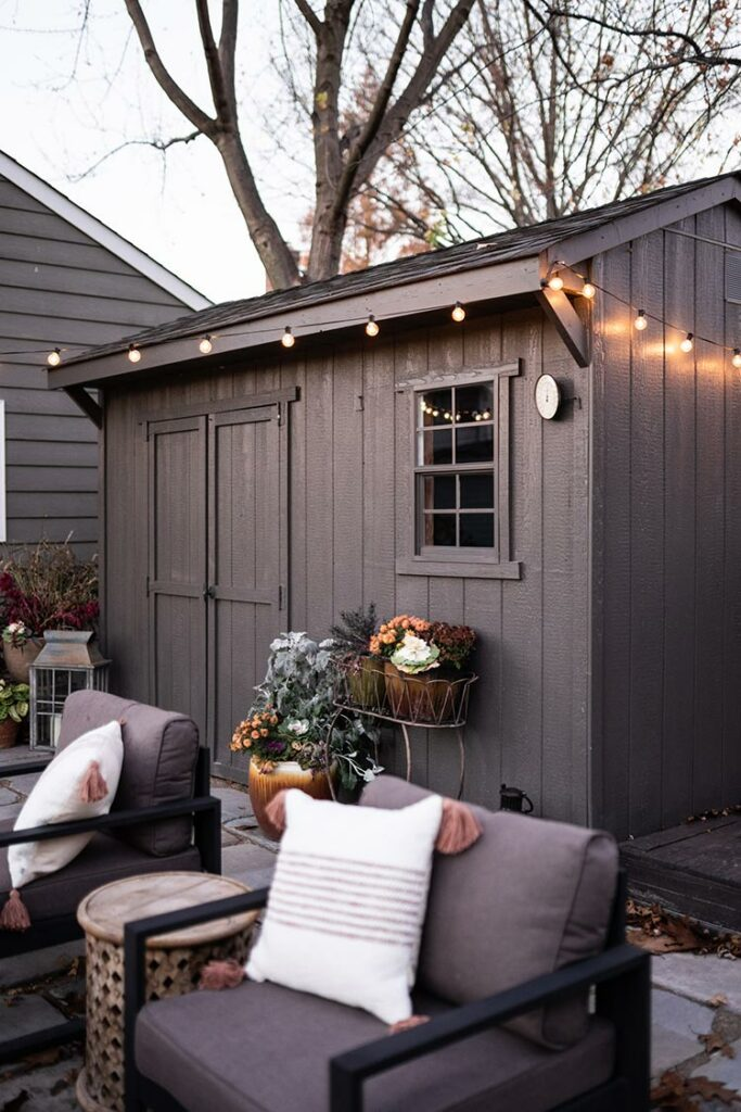 an exterior shot of a backyard shed with string lights