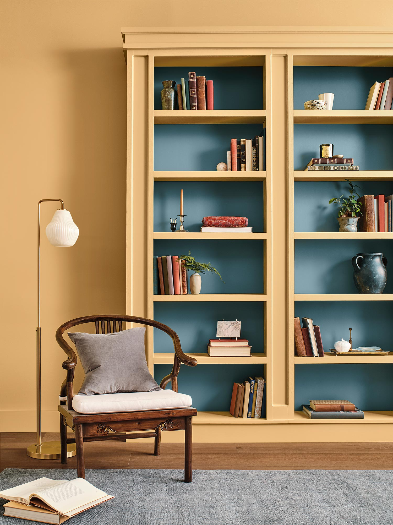 Reading area near a bookshelf painted in yellow and blue: Tarnished Trumpet SW 9026 and Blustery Sky SW 9140.