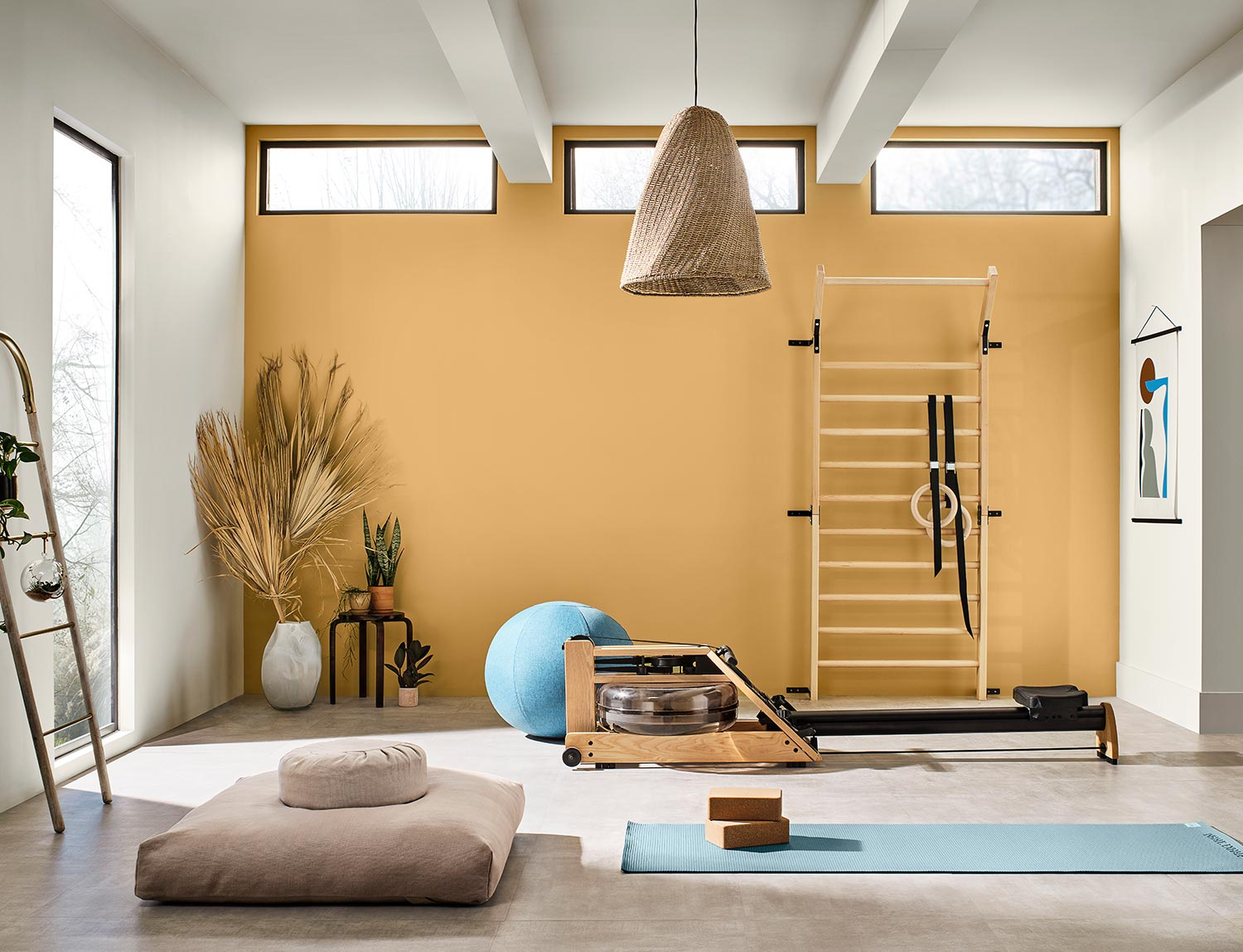 Home gym with equipment, plants and a meditation area with accent wall painted a golden hue: Tarnished Trumpet SW 9026.