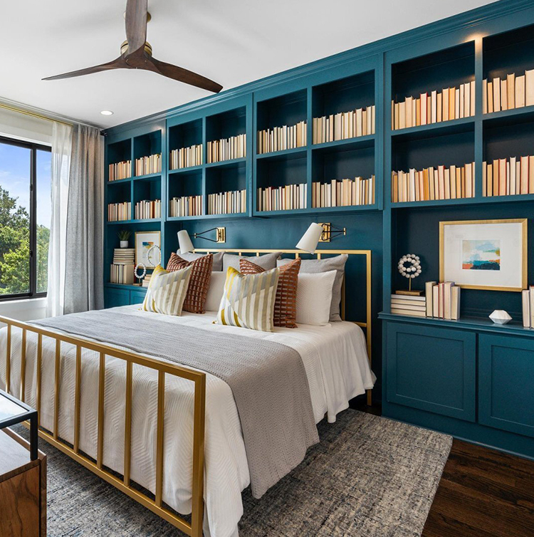 Blue bedroom bookcase with gold bed.
