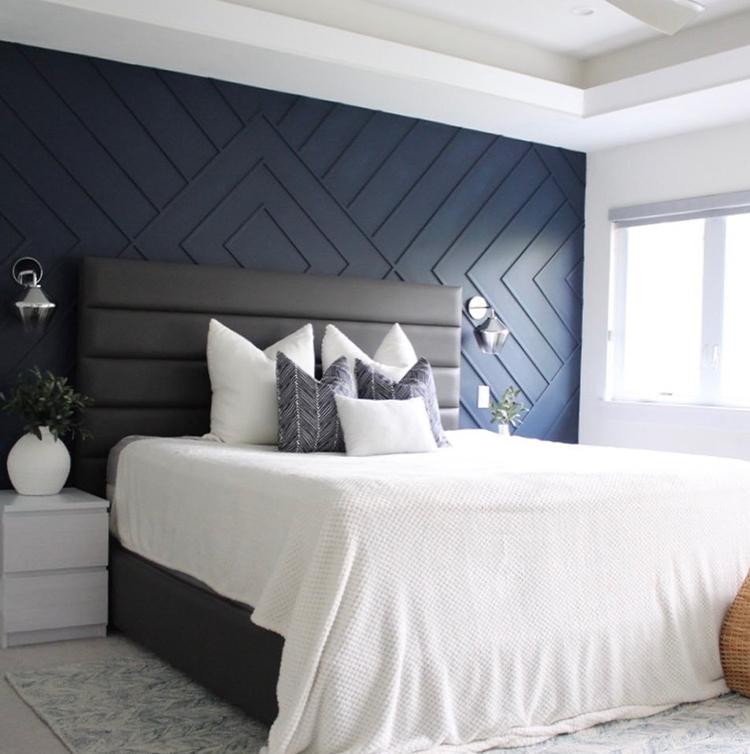 Blue geometric paneled bedroom wall.