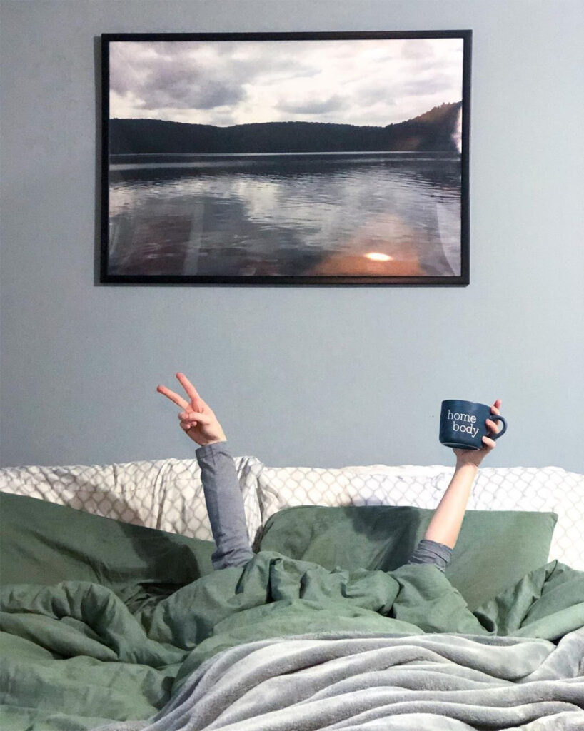 Blue bedroom wall with person in bed holding up peace sign.