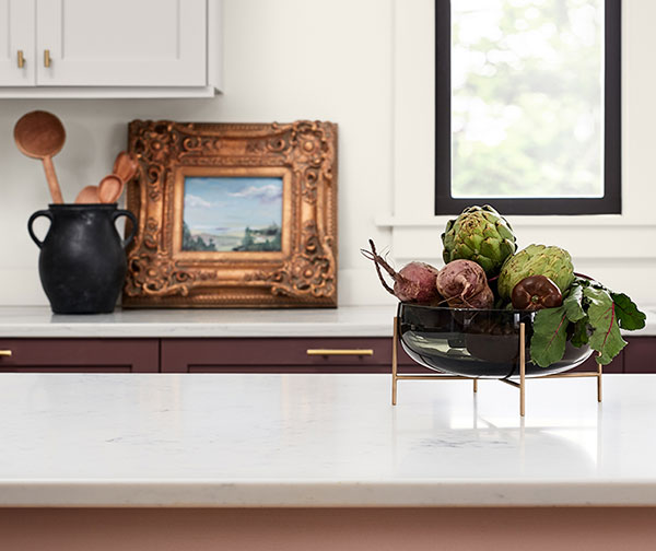 Kitchen vignette showing heritage style concept with wooden spoons in urn, ornate vintage picture frame and bowl of fresh vegetables.