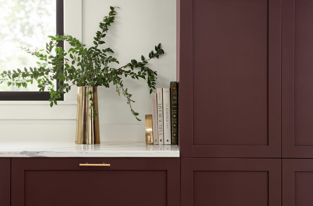 Kitchen cabinets painted Carnelian SW 7580 with gold metal drawer pulls and gold metal vase.