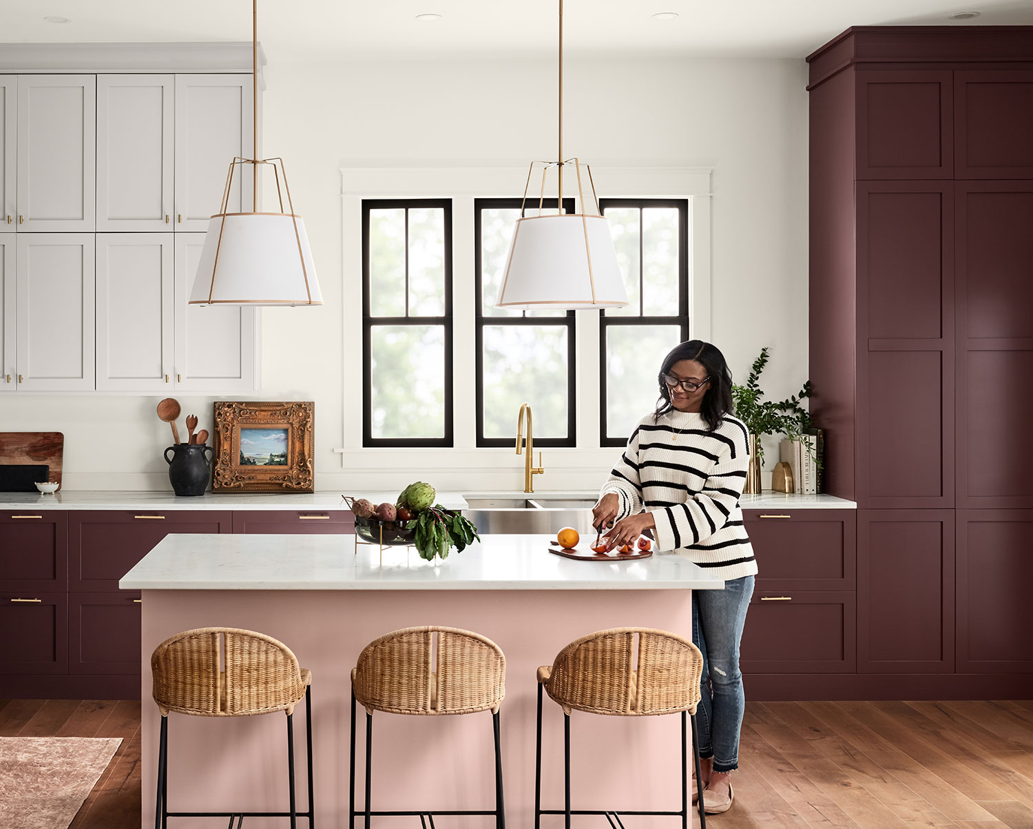 Woman cutting fruit in kitchen with cabinets painted Carnelian SW 7580 and kitchen island painted Pink Shadow SW 0070.