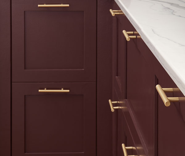Golden metal drawer pulls on kitchen cabinets painted Carnelian SW 7580.