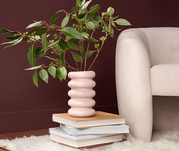 Vintage modern style vignette with chair and vase in front of wall painted Carnelian SW 7580.