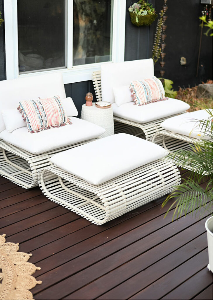 white patio seats and ottomans on a dark brown stained deck
