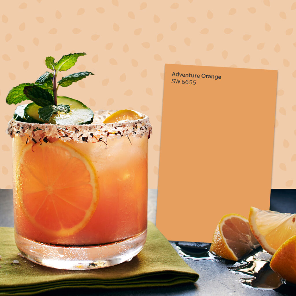 Orange-colored margarita in a glass next to a Sherwin-Williams Adventure Orange SW 6655 color card