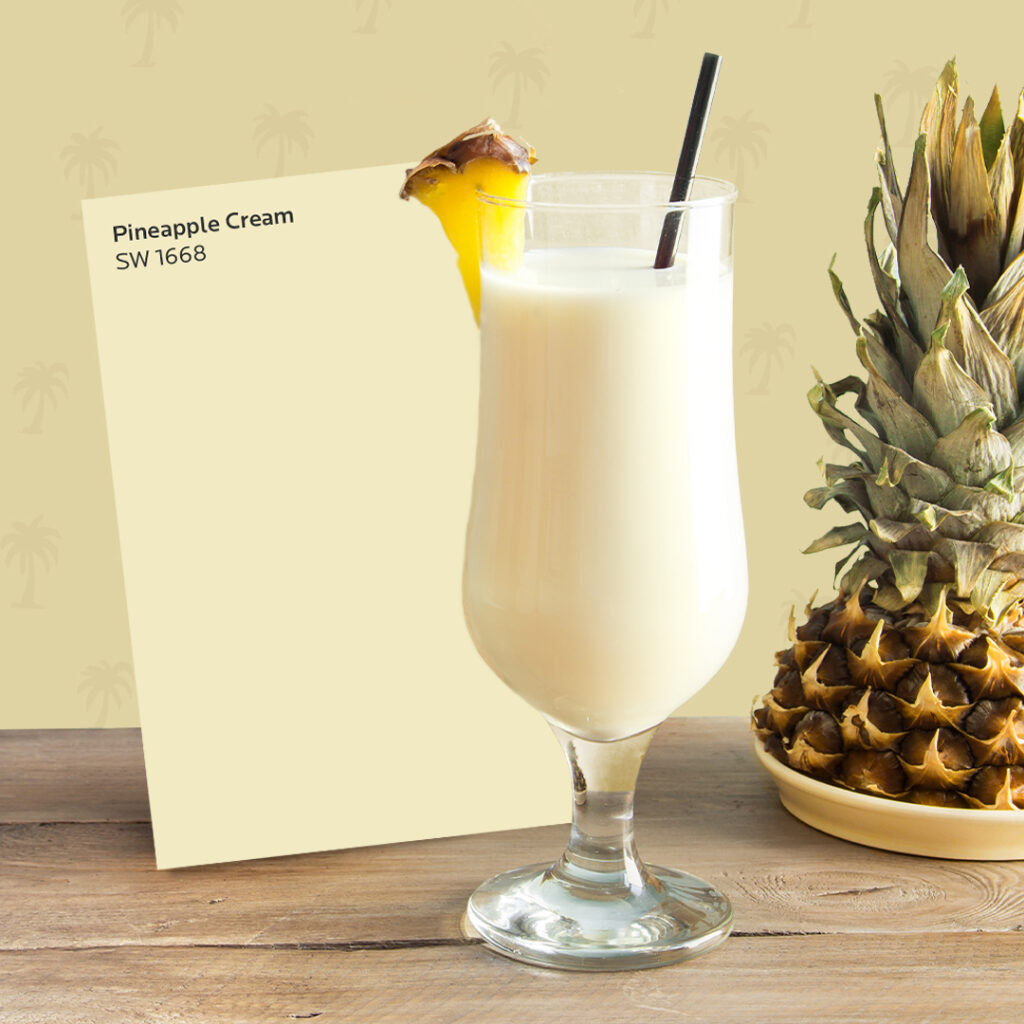 Frozen, blended piña colada in a tall cocktail glass next to a Sherwin-Williams Pineapple Cream SW 1668 color card