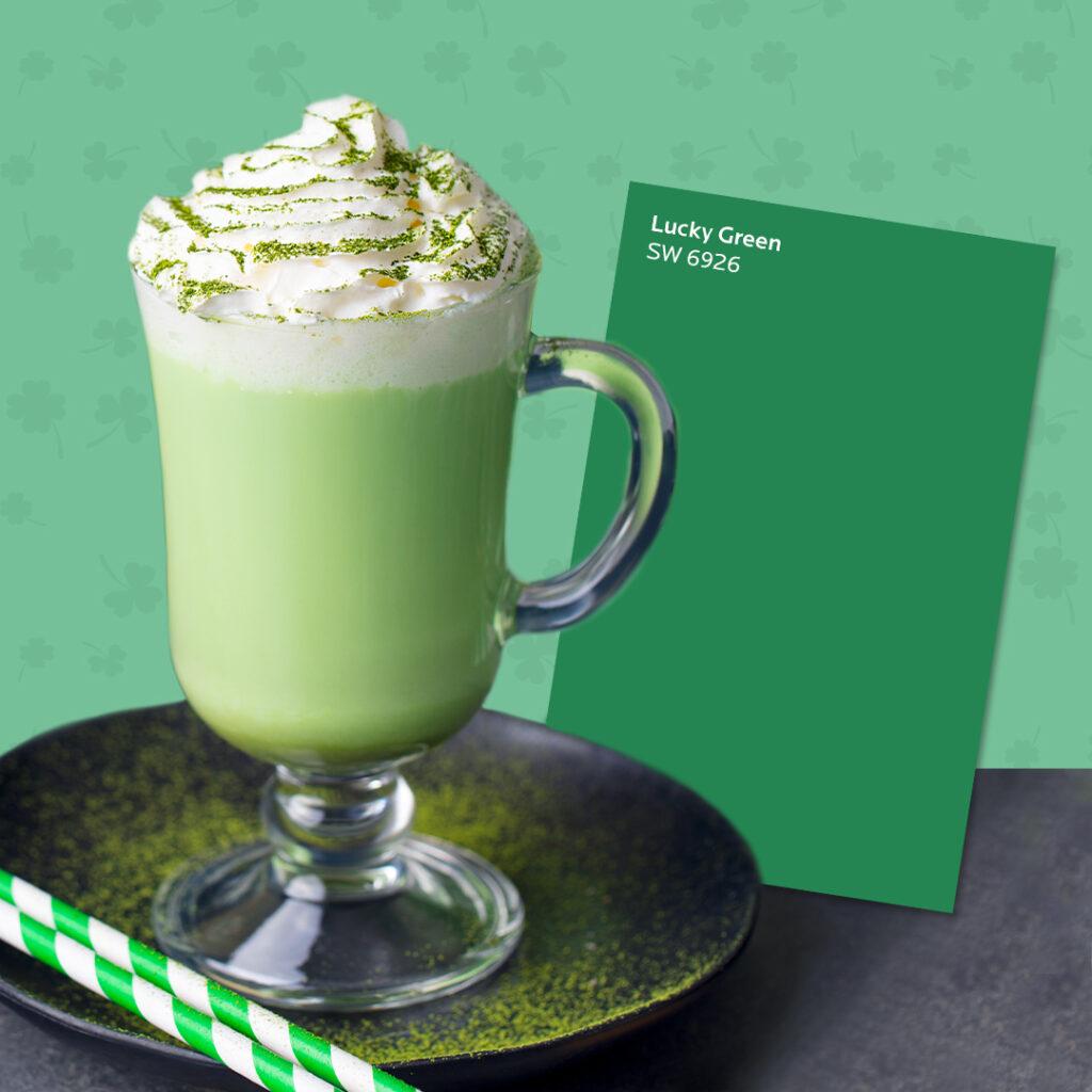 Creamy, green milkshake in a mug next to a Sherwin-Williams Lucky Green SW 6926 color card