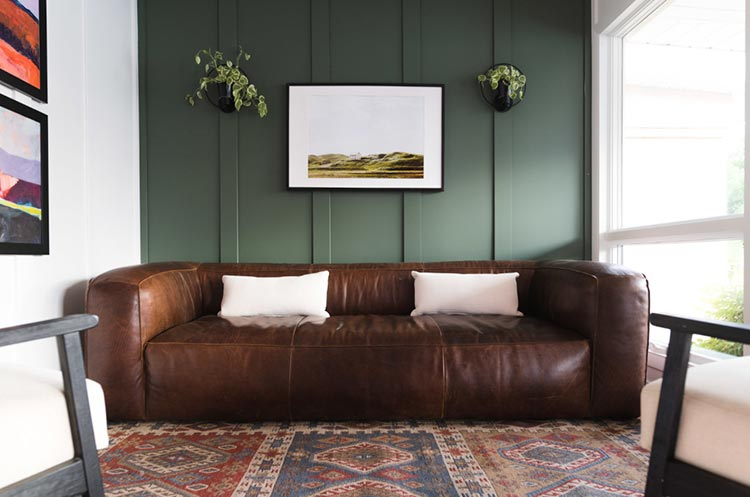 Vignette of a seating area with a green wall with paneled accents.